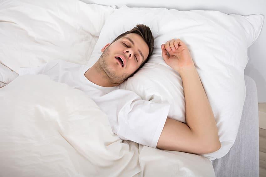 man laying in bed, snoring